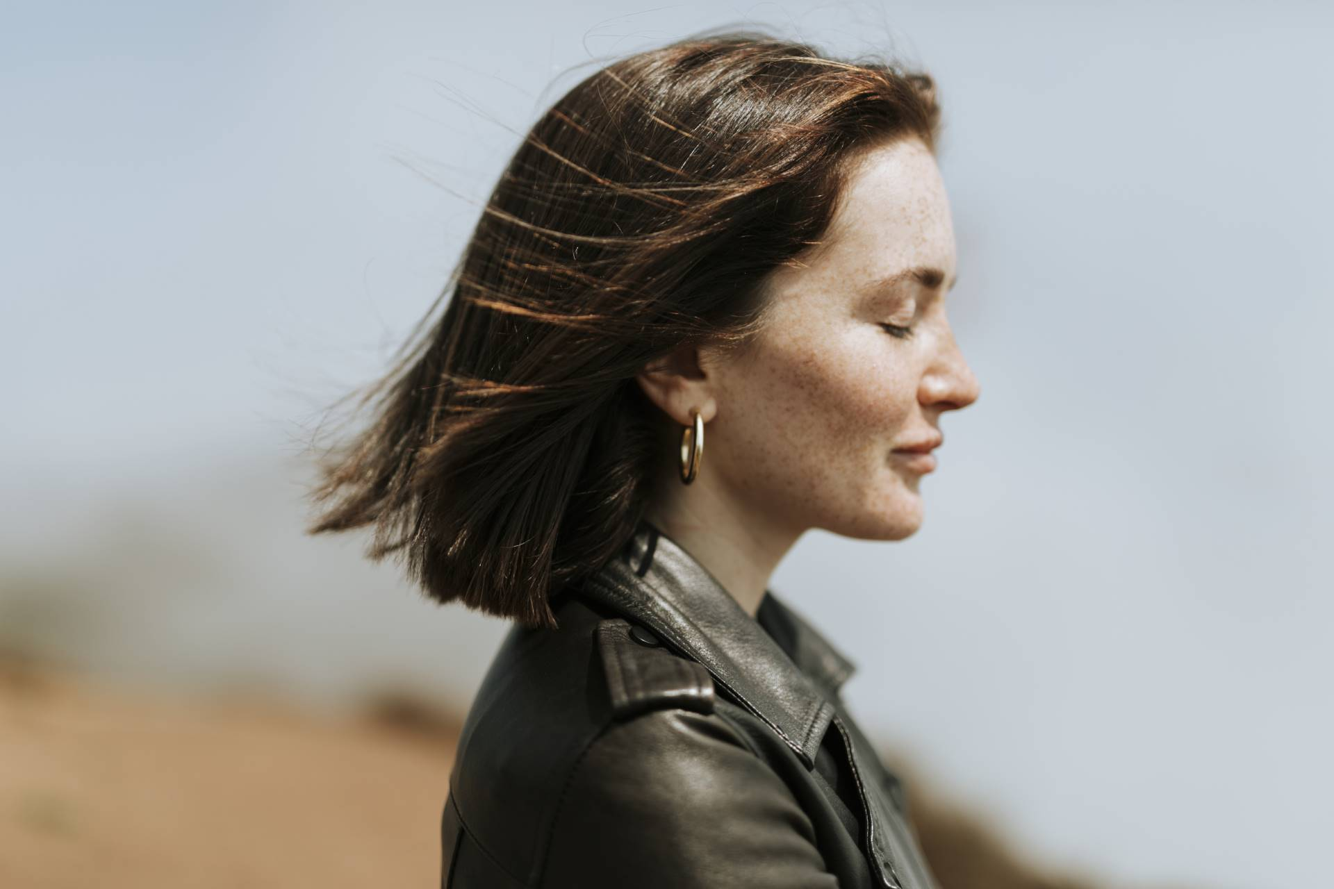 Side view of  a woman in leather jacket standing in a park